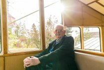 Germany, Dresden, senior man sitting in cable railway — Stock Photo