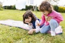 Две девушки играют вместе на лугу — стоковое фото