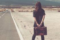 Jovem com mala andando em uma estrada — Fotografia de Stock