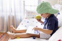 Kleiner Junge sitzt auf der Couch mit einem Apfel mit digital-Tablette — Stockfoto