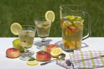 Peach iced tea in carafe, lemon, ice, mint leaves and peaches — Stock Photo