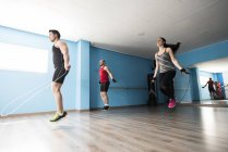 Sporty people skipping rope in fitness room — Stock Photo