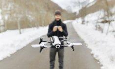 Espagne, Asturies, homme naviguant drone dans les montagnes enneigées — Photo de stock