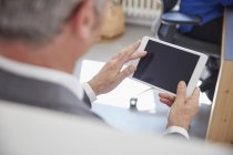 Mature man using digital tablet in office — Stock Photo