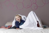 Portrait of laughing little boy sitting on parents' bed beside his sister hiding under a sheet — Stock Photo
