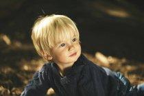 Маленький мальчик в лесу, портрет крупным планом при солнечном свете — стоковое фото
