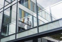 Три бизнесмена за стеклянным фасадом, проход — стоковое фото