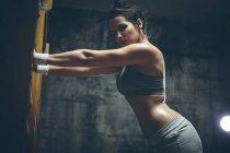 Atleta feminina, exercitando-se nas barras de parede — Fotografia de Stock
