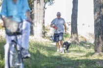 Senior man walking his dog in forest — Stock Photo