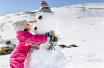 Happy girl playing with snowmen in winter — Stock Photo
