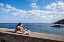 Атлетическая девочка-подросток, растянувшаяся у океана — стоковое фото