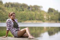 Ritratto di giovane donna seduta su un molo al lago — Foto stock
