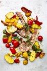 Côtelettes d'agneau, pommes de terre et légumes du four sur une surface altérée blanche — Photo de stock