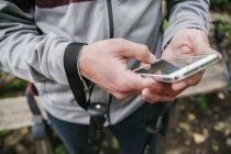 Сербия, Раковац, молодой человек, использующий смартфон во время похода — стоковое фото