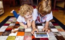 Dos chicos tumbados en el suelo en casa jugando con una tableta digital - foto de stock