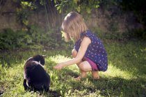 Girl sitting with cat in grassy garden — Stock Photo