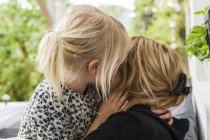 Blond little girl kissing her mother — Stock Photo