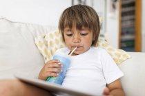 Petit garçon assis sur le canapé en utilisant une tablette numérique tout en buvant quelque chose — Photo de stock