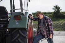 Outil de maintien de l'agriculteur examinant les pneus tracteurs — Photo de stock