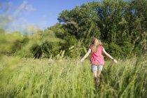 Задній вид підлітка дівчина, що йде на луг — стокове фото