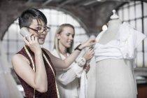 Diseñador de vestido de boda hablando por teléfono y novia de fondo - foto de stock