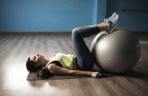 Reife Frau trainiert mit Fitnessball bei Beingymnastik — Stockfoto