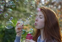 Close-up of Girl making soap bubbles — Stock Photo