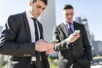 Due uomini d'affari che guardano i cellulari — Foto stock
