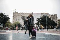 Espagne, Barcelone, jeune femme avec valise marchant sur Placa Catalunya — Photo de stock