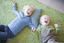 Two laughing little brothers lying on green carpet at home — Stock Photo