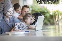 Familia sentado en la terraza mirando juntos portátil en casa - foto de stock