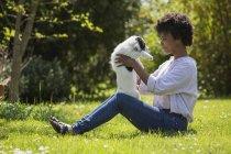 Женщина сидит на лугу и играет с собакой — стоковое фото