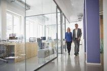 Hombre de negocios y la mujer caminando por el pasillo de la oficina - foto de stock