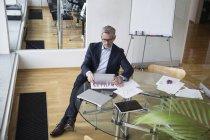 Successful businessman sitting in board room using digital tablet — Stock Photo