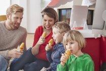Familia feliz con paletas y coche modelo en la sala de estar - foto de stock