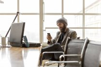 Young businessman wearing beanie hat using smartphone in office — Stock Photo
