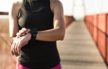 Sportive woman looking at smartwatch on a bridge — Stock Photo