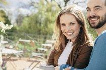 Ritratto di giovane coppia felice seduta al caffè marciapiede — Foto stock