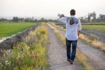 Jeune homme marchant sur le chemin du champ portant des pelles — Photo de stock