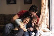 Padre e i suoi figli giocare in casa — Foto stock