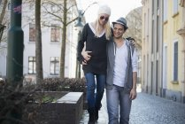 Strolling couple embracing while walking at city street — Stock Photo