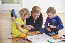 Father lying on floor with children painting — Stock Photo