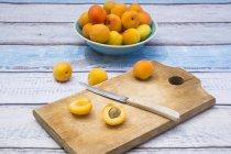 Ganze und halbierte Aprikosen auf Schneidebrett — Stockfoto