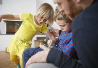Father and two children using digital tablet — Stock Photo