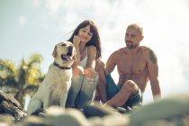 Couple assis avec leur chien sur la plage — Photo de stock