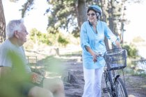 Elderly woman with bicycle and senior man having a break in forest — Stock Photo