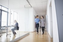 Two businesswomen walking and talking in office hall — Stock Photo