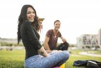 Freinds sitting on grass having fun — Stock Photo