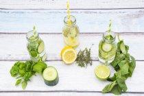 Три стеклянные бутылки воды со вкусом различных фруктов и трав — стоковое фото