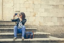 Female tourist sitting on steps of Church of the Assumption taking photo — Stock Photo